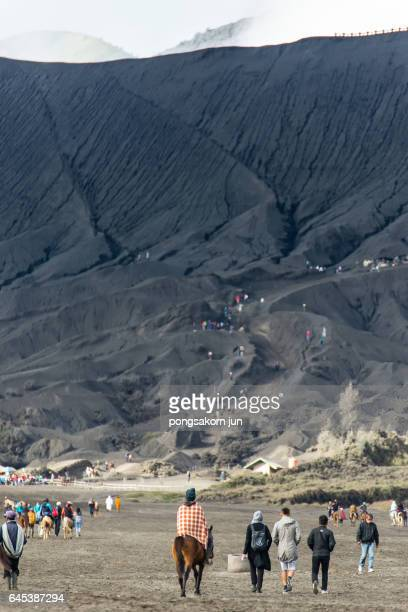 tourists riding horse up to bromo volcano crater - bromo crater stock photos and pictures