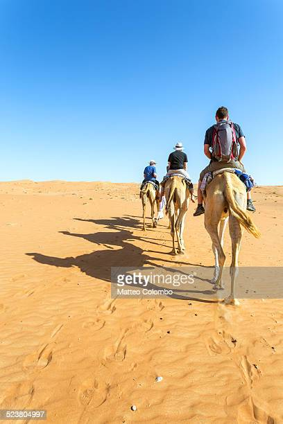 Tourists riding on camel in Wahiba sands desert