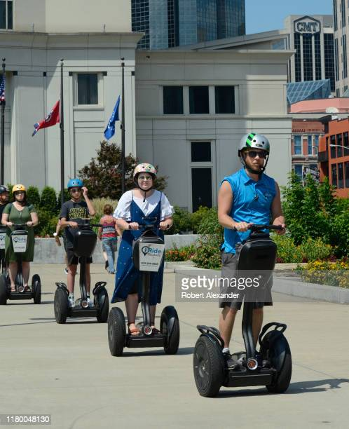 Tourists riding Segway PT personal transporters follow their guide as they roll through downtown Nashville, Tennessee.