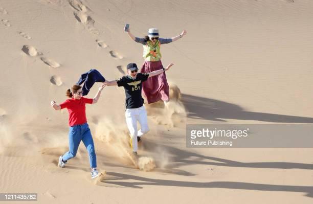 Tourists run on the sand mountain of Badain Jilin desert Geopark. Inner Mongolia, China, May 1, 2020.- PHOTOGRAPH BY Costfoto / Barcroft Studios /...
