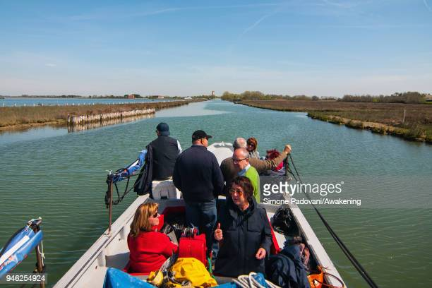 Tourists sail a canal on a boat of a fishing tour organized by Cooperativa San Marco in Burano on April 14 2018 in Venice Italy At the beginning of...