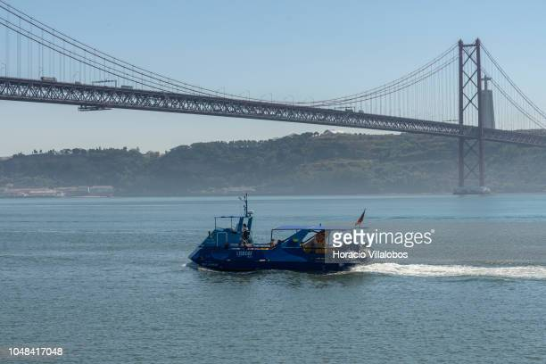 Tourists sail onboard a LISBOAT river cruise motorboat on the Tagus River near 25 de Abril bridge on October 01 2018 in Lisbon Portugal LISBOAT is a...