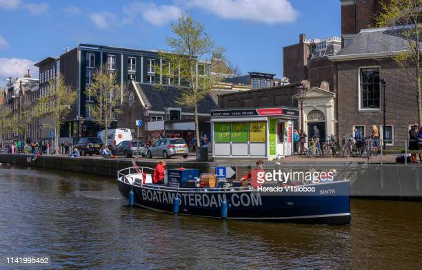 Tourists sail past Anne Frank house while taking a canal cruise on April 11 2019 in Amsterdam The Netherlands The number of visitors some ten...