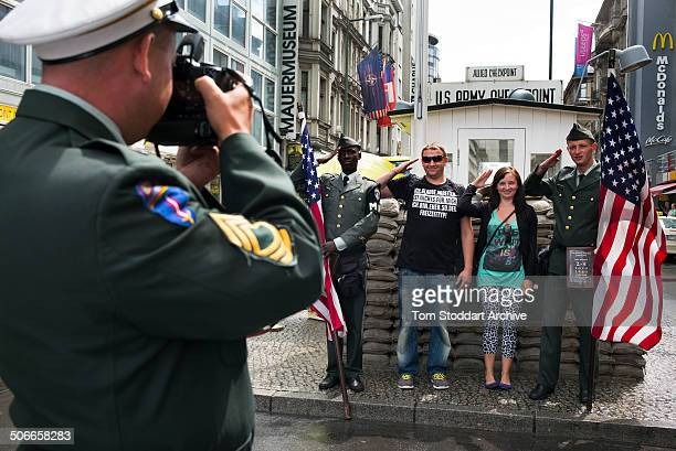 Tourists salute while having their souvenier photographs taken with actors dressed as American military police at Checkpoint Charlie the most well...
