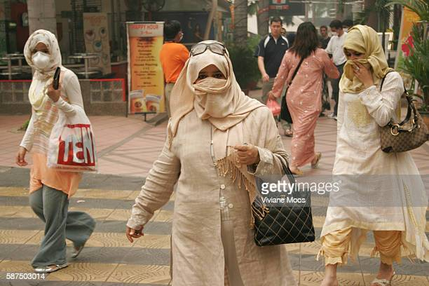 Tourists seek protection from the deadly haze by covering their nose and mouth while walking along Bukit Bintang, Kuala Lumpur's elegant shopping...