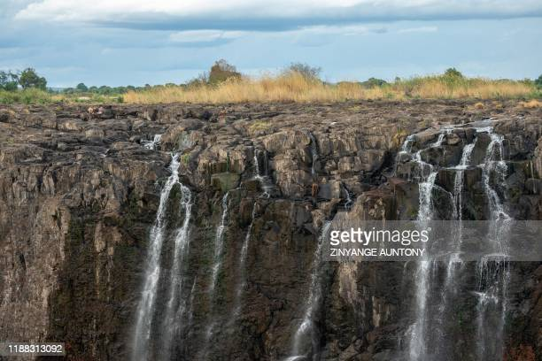 Tourists seen sitting at the Zambezi river at the edge of the Victoria Falls looking into Zimbabwe in Victoria Falls on December 10 2019 The Victoria...