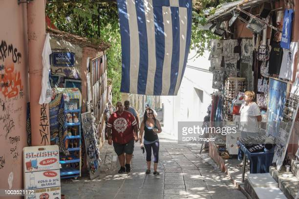 Tourists seen walking under a Greek flag as they walk past a shop