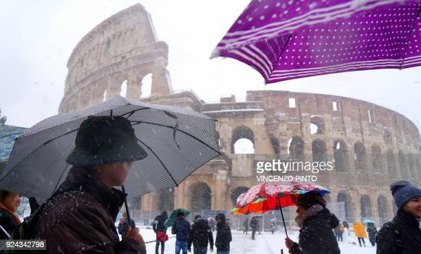 Tourists shed under umbrellas as they visit the ancient Colosseum during a snowfall in Rome on February 26 2018 / AFP PHOTO / Vincenzo PINTO