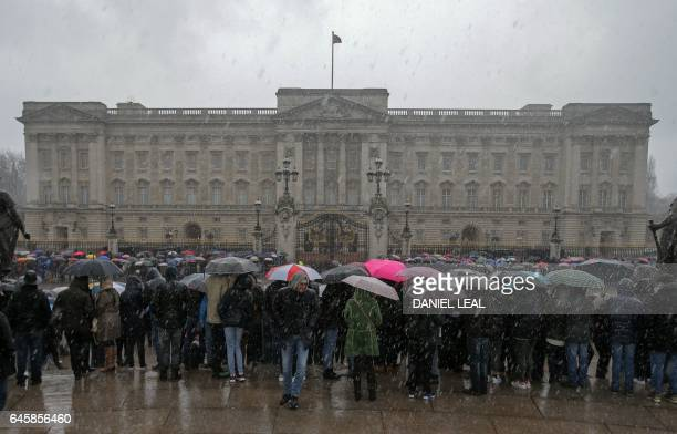 Tourists shelter from the rain beneath umbrellas as they line The Mall waiting to watch the Changing of the Guard ceremony outside Buckingham Palace...