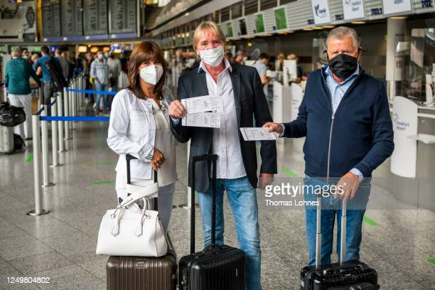 Tourists show their boarding pass after check in for a TUIfly flight to Mallorca at Frankfurt Airport on the first day that package tours are...