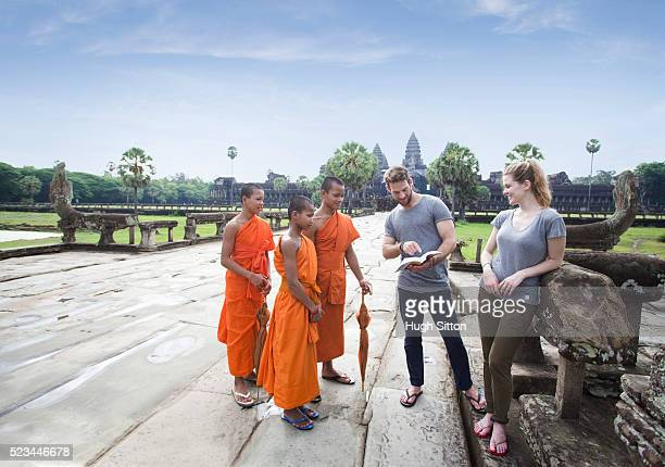 tourists showing book to local monks, angkor wat, cambodia - hugh sitton stock pictures, royalty-free photos & images