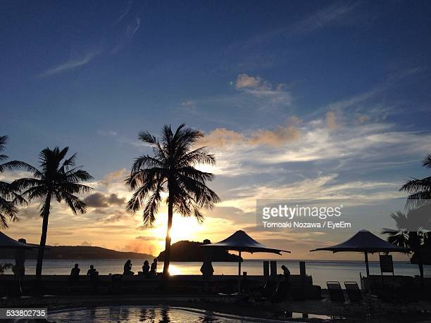 Tourists Silhouetted Against Sunset Overlooking Sea At Resort