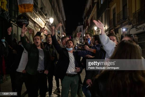 Tourists sing outside a bar as the curfew starts during the Coronavirus pandemic on March 20, 2021 in Madrid, Spain. Whilst Covid-19 infection...