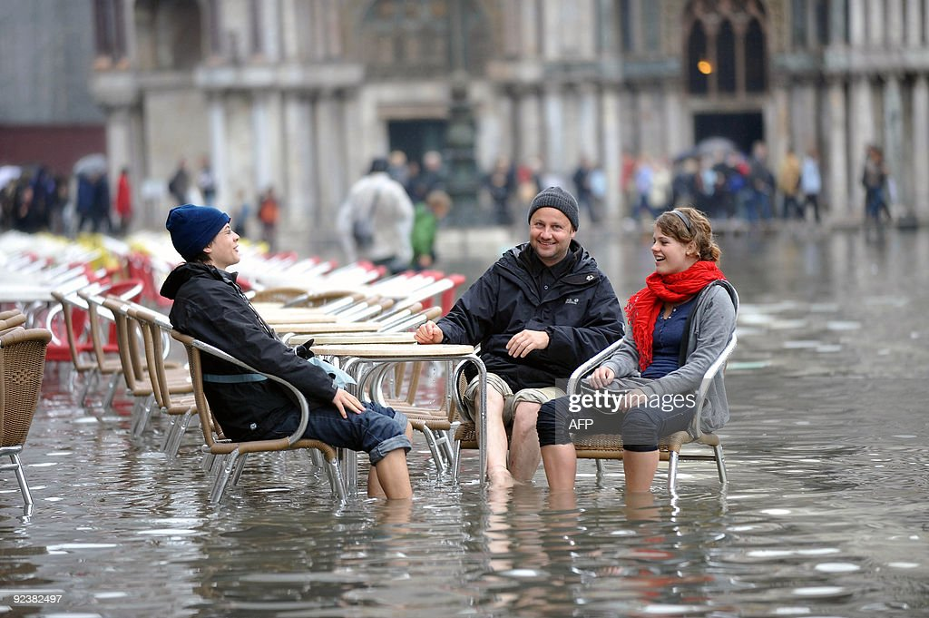 Tourists sit at a cafe terrace on the fl : News Photo