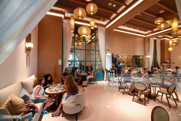"""Tourists sit at a restaurant at the Al Naseem hotel in the Gulf emirate of Dubai in the United Arab Emirates, on July 7, 2020. - With a """"welcome""""..."""