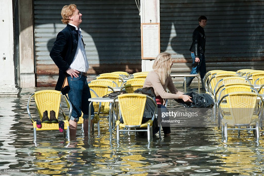 Tourists sit at a table at a cafe terrace on the flooded Piazza San Marco on November 5, 2013 in Venice, Italy.The high tide, or acqua alta as it is locally known, stood at 105 centimeters this morning.