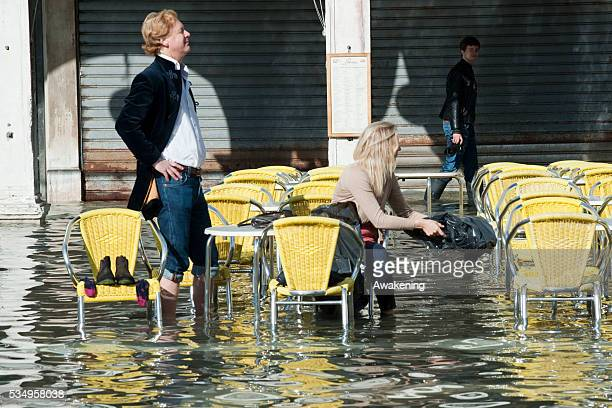 Tourists sit at a table at a cafe terrace on the flooded Piazza San Marco on November 5 2013 in Venice ItalyThe high tide or acqua alta as it is...