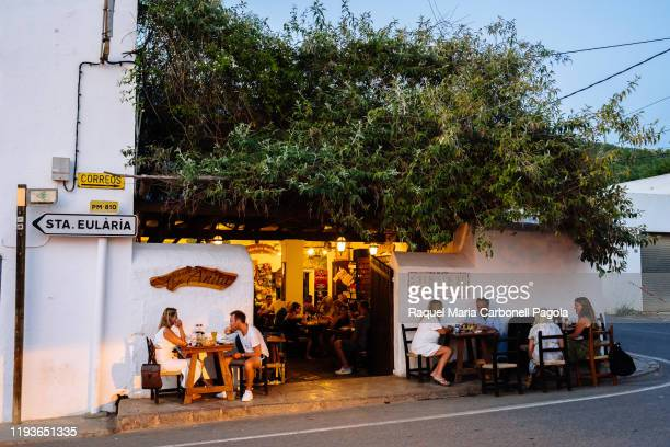 Tourists sit at bar Can Anneta.
