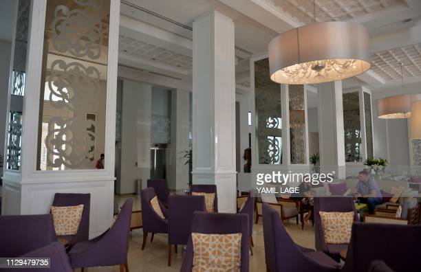 Tourists sit at the lobby of the Gran Manzana Hotel in Havana on February 6 2019 Cuba attracts wealthy tourists with fivestars hotels spas and luxury...