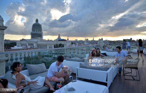 Tourists sit by the swimming pool on the rooftop of the Gran Manzana Hotel in Havana on February 11 2019 Cuba attracts wealthy tourists with...