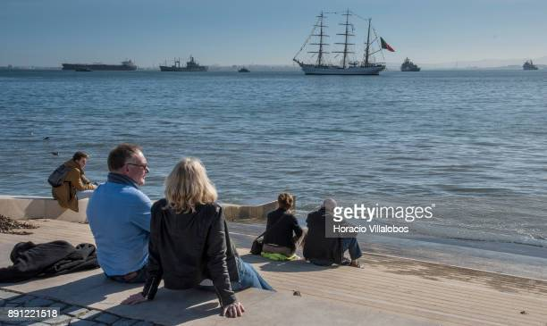 Tourists sit by the Tagus River while Portuguese and foreign ships lay at anchor during the commemoration day of the Portuguese Navy's 700th...