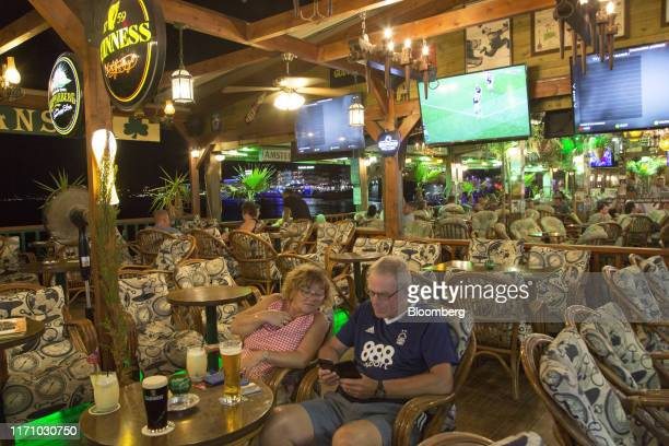 Tourists sit in a bar in Hersonissos, on the island of Crete, Greece, on Tuesday, Sept. 24, 2019. Like Crete, Europes other tourist hot-spots are...