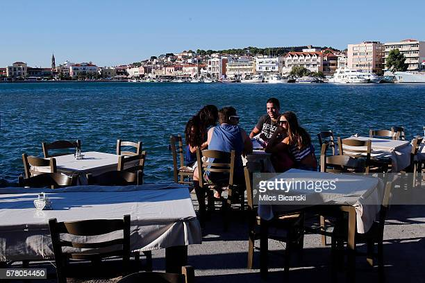 JULY Tourists sit in an almost empty restaurant in the port on July 19 2016 in Mytilini Lesvos island Greece The increase in refugees arriving on the...