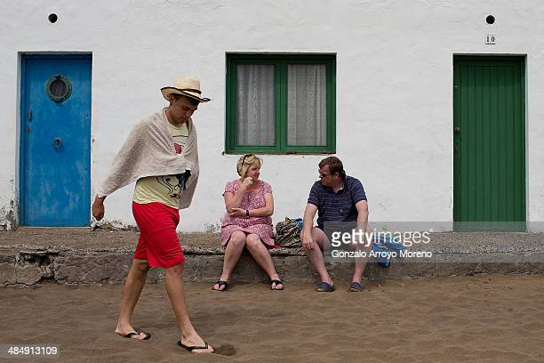 Tourists sit in front of a typical Lanzarote house on April 13 2014 at Puerto del Carmen in Lanzarote Spain Lanzarote where British Prime Minister...