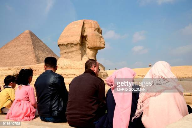 Tourists sit in front of the Giza Sphinx at the Giza Pyramids complex on the southwestern outskirts of the Egyptian capital Cairo on February 15 with...
