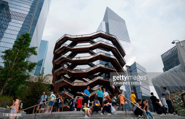 Tourists sit in front of the Vessel at Hudson Yards on August 13 2019 in New York City