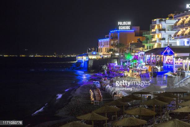 Tourists sit in restaurants and bars along the seaside in Hersonissos, on the island of Crete, Greece, on Tuesday, Sept. 24, 2019. Like Crete,...