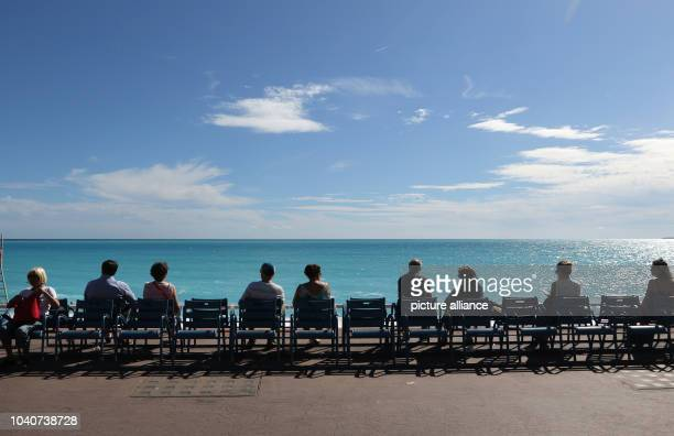 Tourists sit on a bench on the beach promenade 'Promenade des Anglais' in Nice France 14 September 2016 Photo Ina Fassbender/dpa | usage worldwide