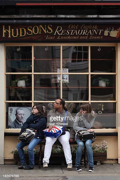 Tourists sit on a bench outside Hudson's Old English Restaurant on Baker Street on April 5 2012 in London England The restaurant is situated next to...