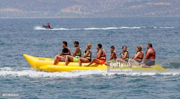 Tourists sit on an inflatable banana boat in Izmir Turkey on July 25 2017 In Summer's extreme hot days people try to cool themselves off with various...