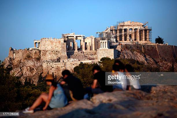 Tourists sit on rocks with a view of the Parthenon temple on Acropolis Hill in Athens Greece on Tuesday Aug 20 2013 A third aid program for Greece...