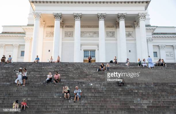 Diners sit on the deck of a restaurant aboard a vessel in view of the Uspenskin cathedral in Helsinki Finland on Monday July 16 2018 The nation's...