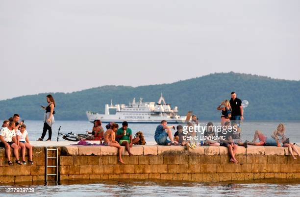 Tourists sit or walk on a pier at sunset in Zadar, on the Adriatic coast on August 6, 2020. - A large number of tourists visited the Zadar Riviera,...