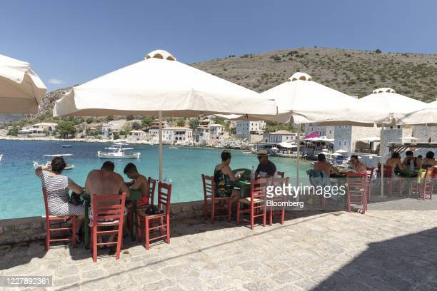 Tourists sit outside a tavern by the sea at Limeni village of Mani peninsula, Peloponnese region, Greece on July 31, 2020. Some travelers from...