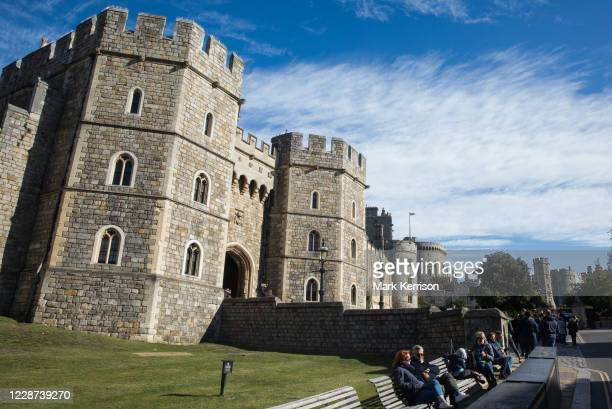 Tourists sit outside Windsor Castle where special precautions have been taken by the Royal Collection Trust to help protect visitors from the...