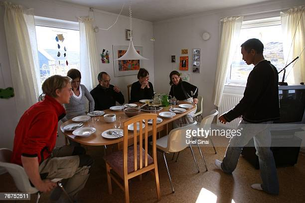 Tourists sit to have breakfast at Arne Lange's home August 27 2007 Ilimanaq Greenland Lange a 39yearold Inuit fisherman who has largely given up...