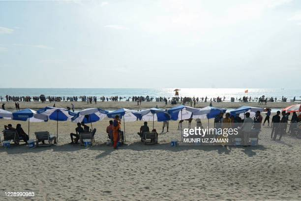 Tourists sit under umbrellas on a beach in Cox's Bazar on October 10, 2020.