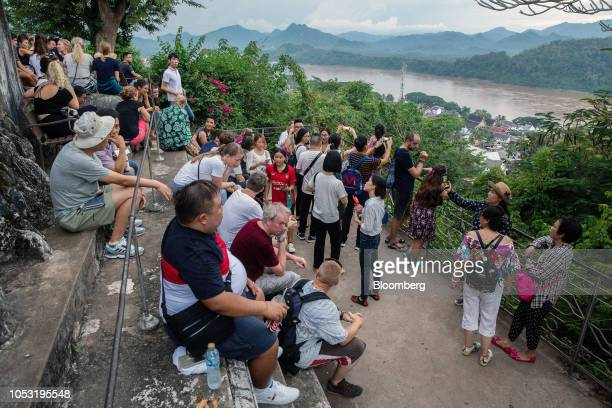 Tourists sit waiting for a sunset view at Mount Phousi in Luang Prabang Laos on Sunday Oct 21 2018 Laos's economy is set to expand at 7 percent this...