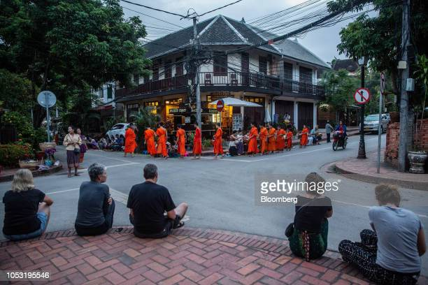 Tourists sit watching as monks collect alms at a ceremony in Luang Prabang Laos on Monday Oct 22 2018 Laos's economy is set to expand at 7 percent...