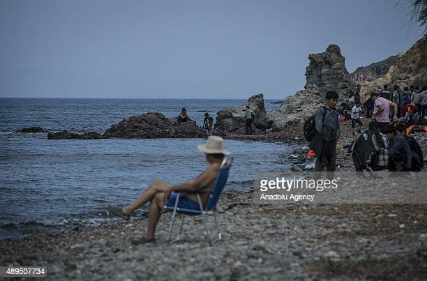 A tourists sits on the beach after the refugees arrived in Greece's Lesbos island on September 22 2015 Refugees who begin a journey with a hope to...