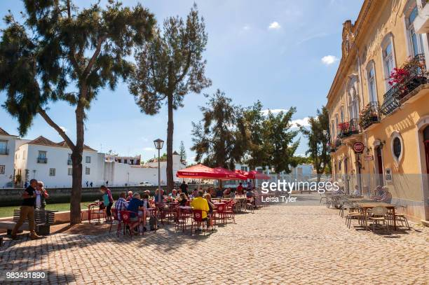 Tourists sitting by the Gilao River in Tavira, a Moorish- built town on the southern coast of Portugal. The town is a popular tourist destination.
