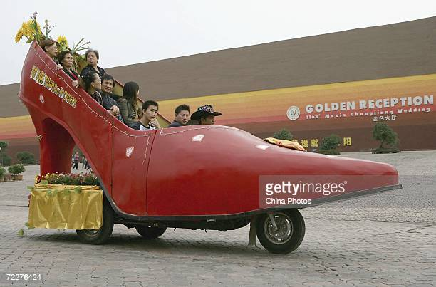 Tourists sitting in a highheel shoe shaped tourist car tour the Foreigner Street section of the Nanbin Road on October 27 2006 in Chongqing China...