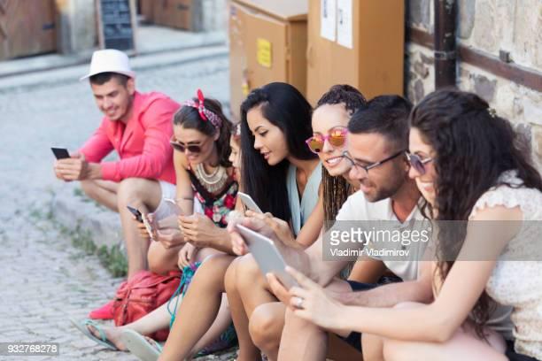 Touristen sitzen in einer Reihe auf Straße und SMS