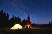 Tourists sitting near campfire under starry sky.
