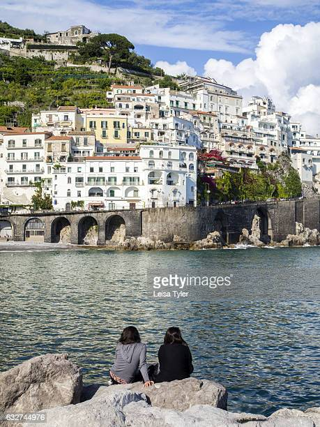 Tourists sitting on Amalfi's breakwater Italy
