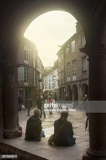 Tourists sitting under stone arches, old town Santiago de Compostela.